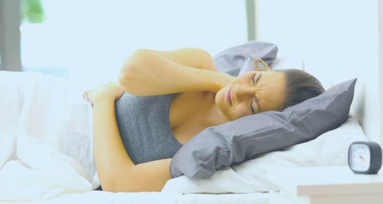 mujer con dolor en la cama